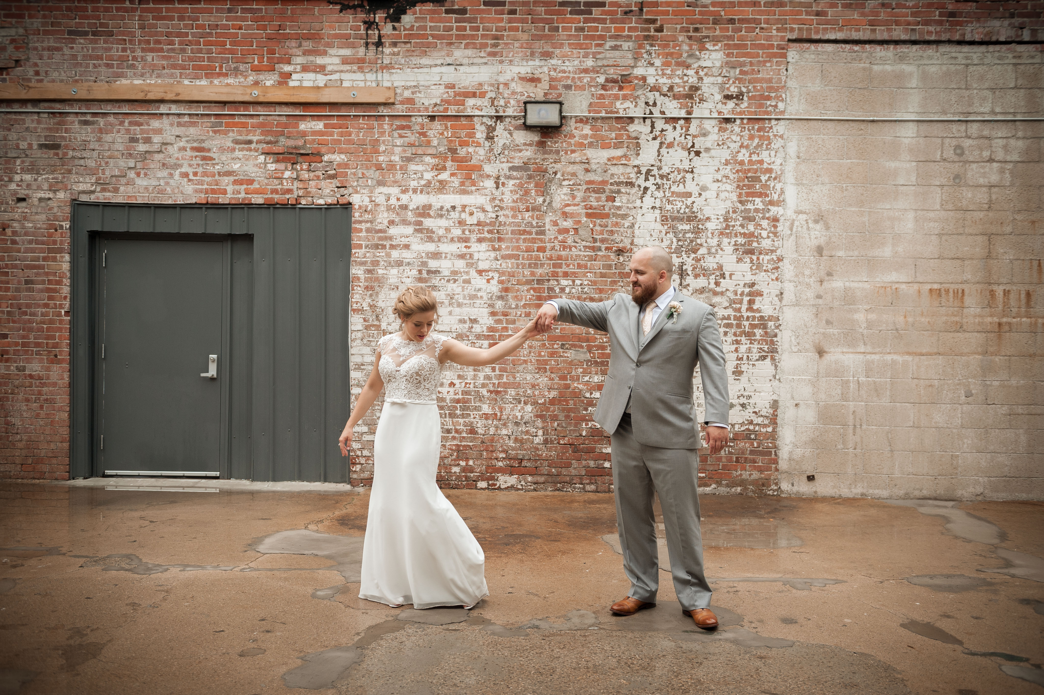 Bride and groom dancing in front of rustic brick warehouse