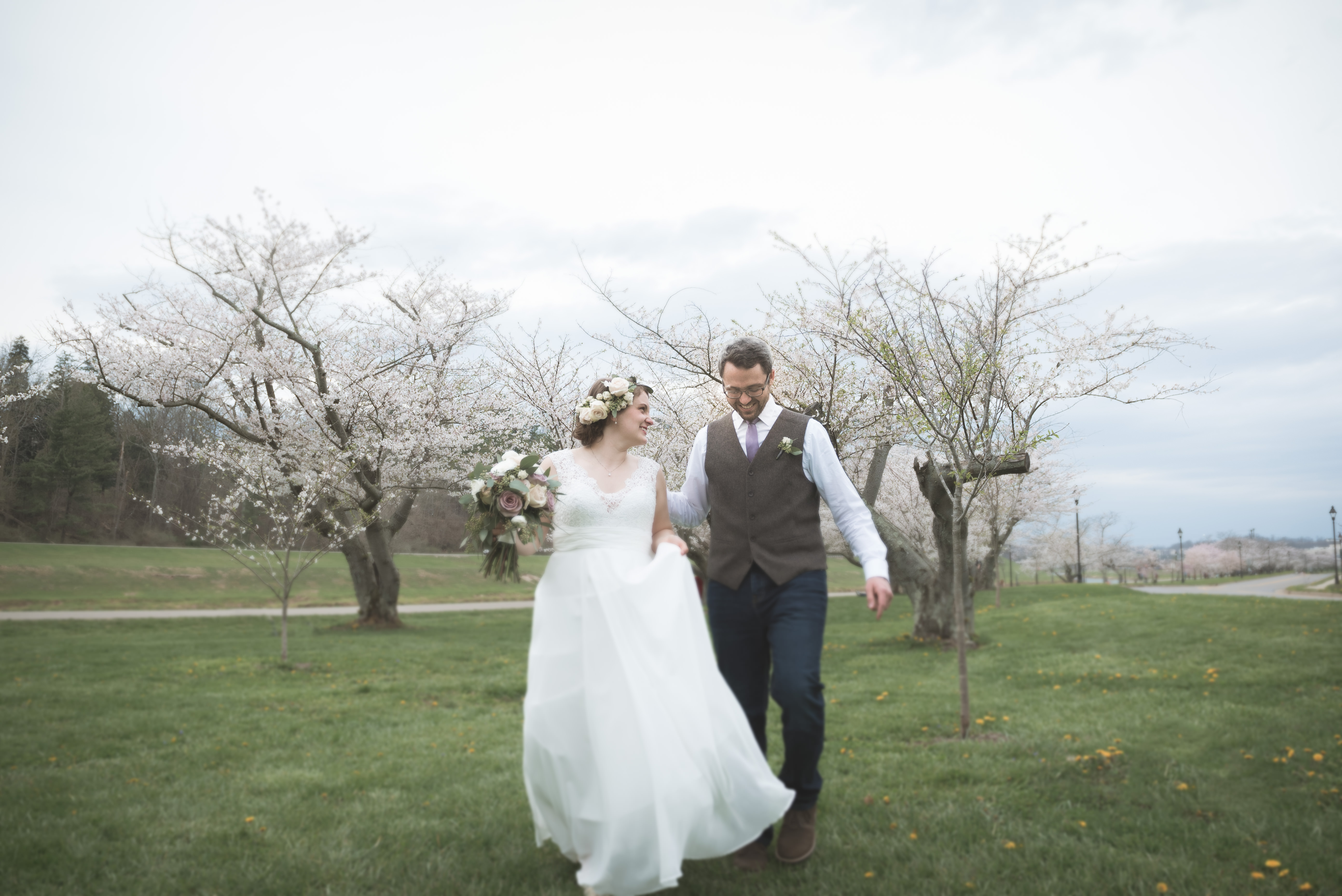 wedding bride and groom walk under cherry blossom trees in the spring in athens ohio