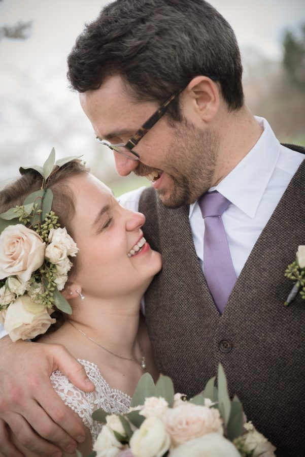 bride wears flower crown under cherry blossom trees in athens ohio