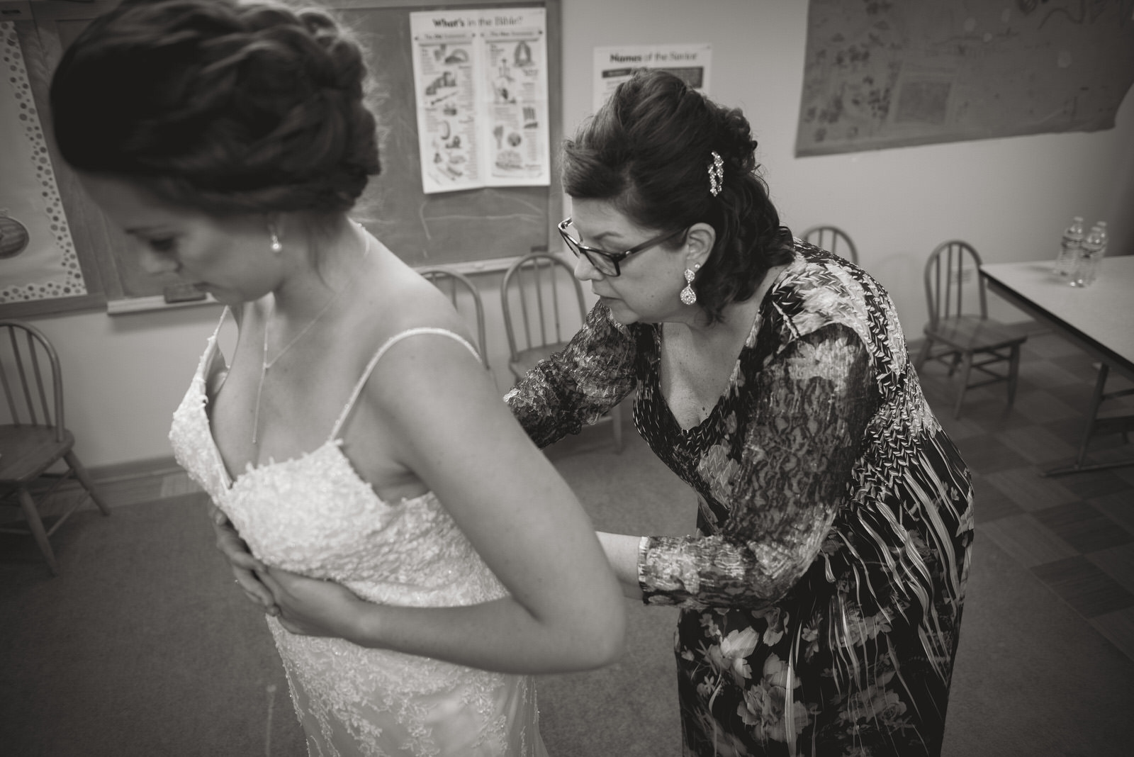 mother of bride putting on wedding dress in nashport ohio
