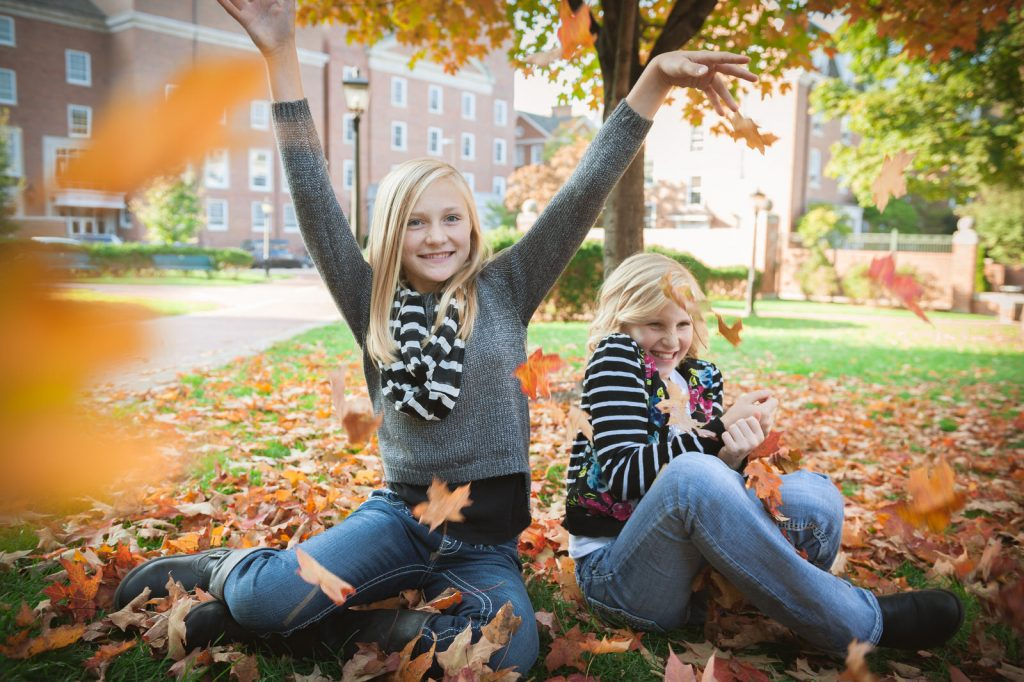sisters play in leaves in uptown athens ohio near court stree
