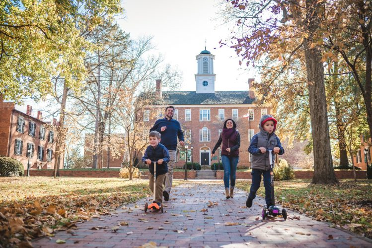 Family playing on Ohio University College Green with their family portraits